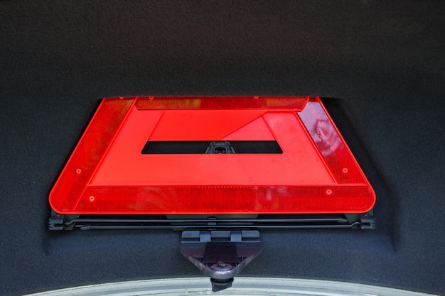 A red folded emergency sign lies in the trunk.