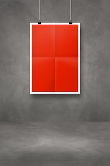 Red folded poster hanging on a dark concrete wall with clips. blank mockup template