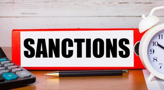 Красная папка для бумаг с текстом санкции, белый будильник, калькулятор и ручка на рабочем столе. бизнес-концепция