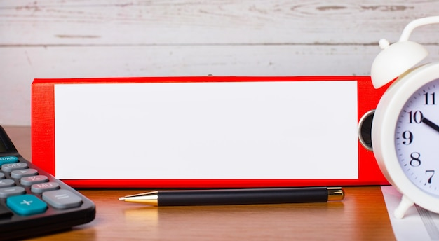 Red folder for papers with place to insert text, white alarm clock, calculator and pen on the desktop
