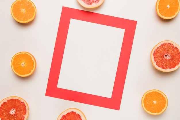 Red frame and sliced juicy grapefruit orange on white surface