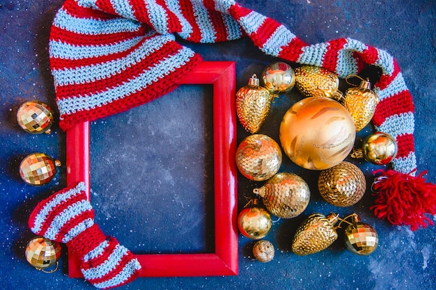 Красная рамка с вязанной полосатой шапкой, галстуком-бабочкой и елочными игрушками на синем фоне. новогодняя планировка квартиры