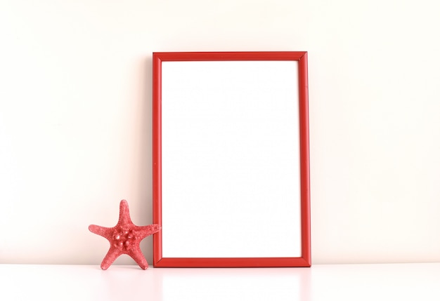 Red frame with sea star, minimal composition on white table.