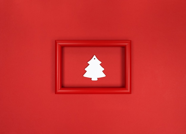 Red frame, with white wooden christmas tree toy inside.