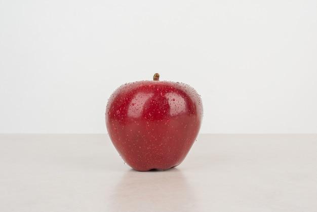 Una mela rossa e fresca su sfondo bianco.