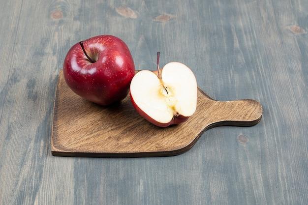 Red fresh apple on wooden board