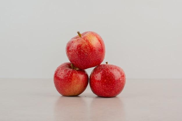 Красные, свежие яблоки на белом столе.
