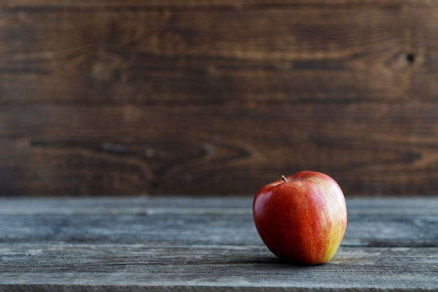 Red fresh bio apple on a wooden rustic table. wood background background.