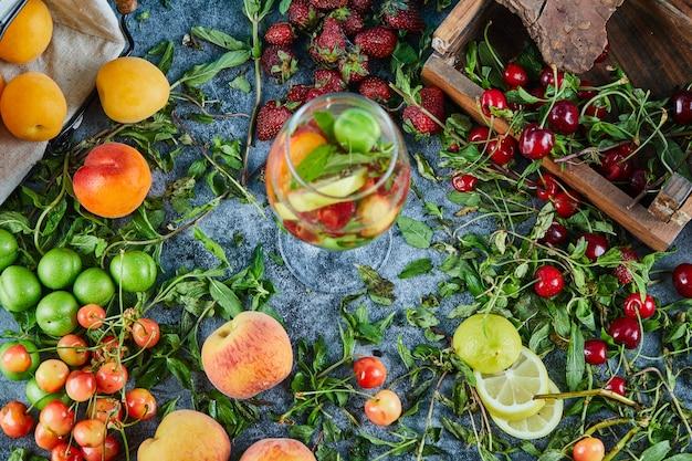 Ciliege fresche rosse sulla scatola di legno con un bicchiere di succo di frutta e frutta fresca