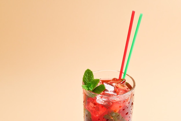 Красный свежий напиток со льдом, грейпфрутом и мятой на бежевом фоне. место для текста или дизайна.