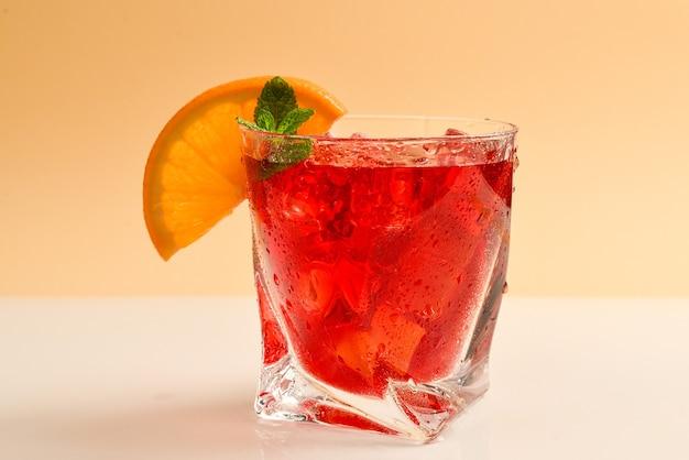 氷、グレープフルーツ、ベージュ色の背景にミントと赤の新鮮な飲み物。テキストまたはデザインのためのスペース。