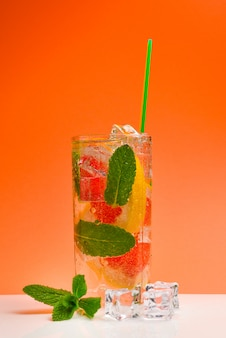 Red fresh drink with ice, grapefruit and min