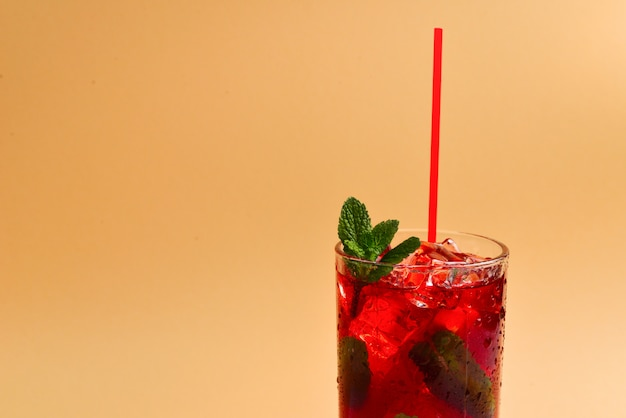 Red fresh drink with ice, grapefruit and mint on an beige background. space for text or design.