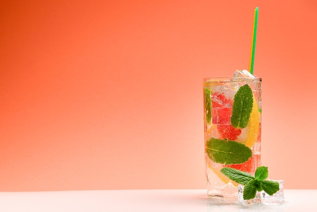 Red fresh drink with ice, grapefruit and mint on an orange background. space for text or design.
