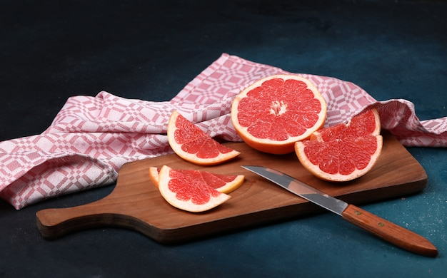 Red fresh grapefruit slices on a wooden board with a knife.