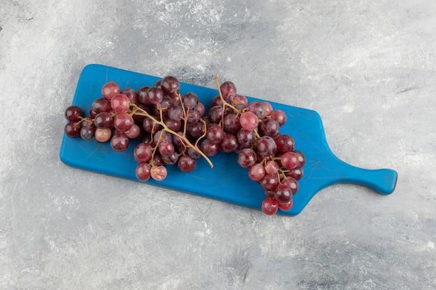 青いまな板の上に置かれた赤い新鮮なブドウ。