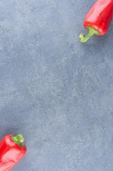Peperoni freschi rossi su marmo.