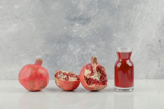白いテーブルの上の赤い新鮮なザクロとフレッシュジュース。