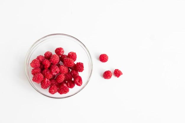Red fresh raspberries in a glass bowl