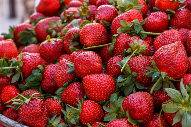 Red fresh ripe strawberries with green leaves