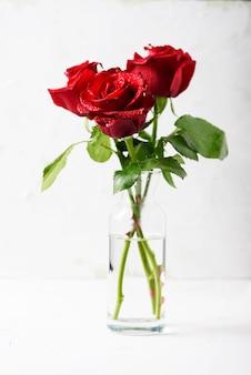 Красные свежие розы на белом столе, выборочный фокус
