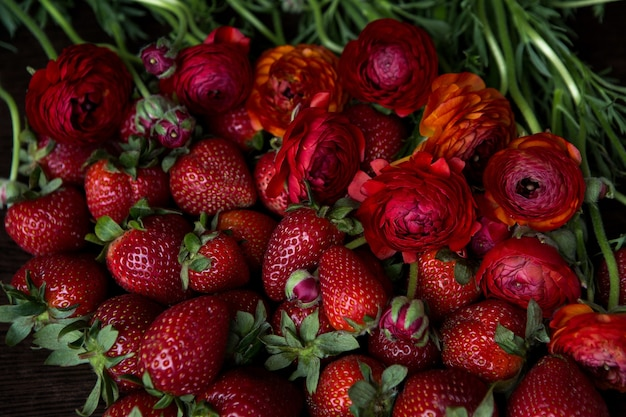 赤い新鮮なイチゴは赤い花ラナンキュラスの隣にあります
