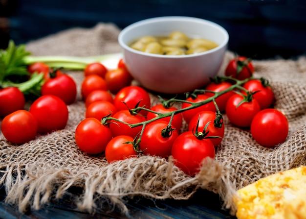 Красные свежие вкусные помидоры черри, зеленый лук, оливки на темном деревенском дереве