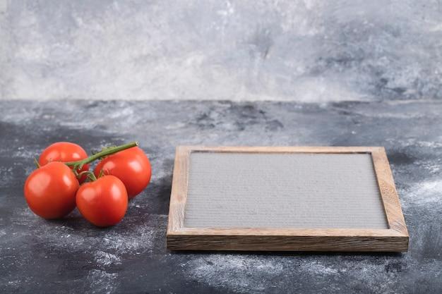Красные свежие помидоры и пустая рамка на мраморной поверхности.