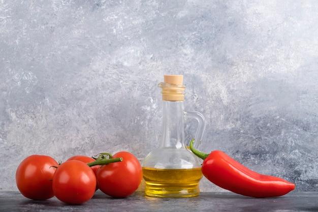 Красные свежие помидоры, перец чили и оливковое масло на мраморной поверхности.