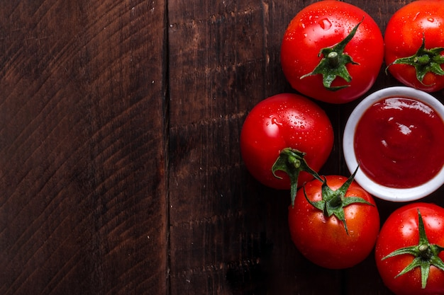 Red, fresh tomatoes and tomato sauce on a dark, wooden background. top view. copy space
