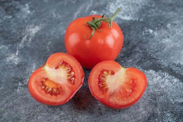 Красные свежие помидоры целиком или порезанными. фото высокого качества