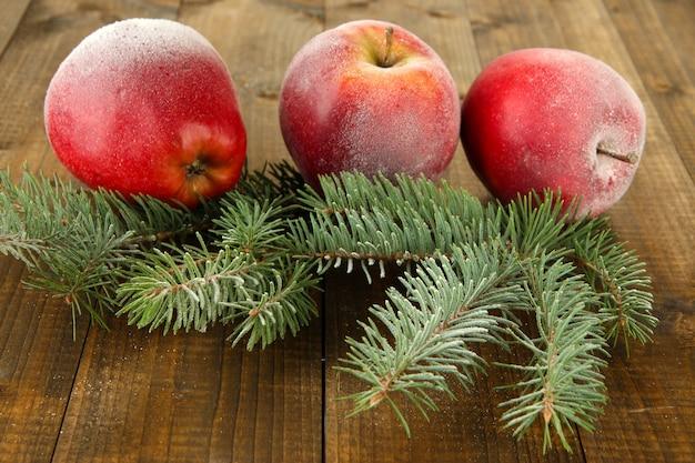 Красные матовые яблоки с еловой веткой на деревянном фоне