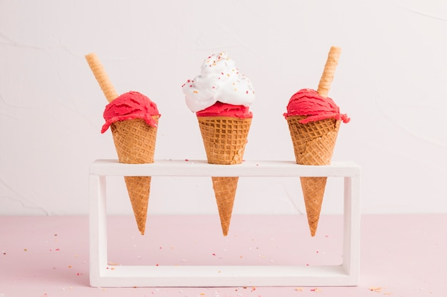 Red frozen ice cream scoop in cones with waffle straw