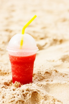 Red fruit icy cocktail in beach sand