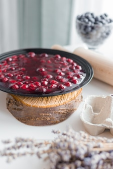 Red fruit jelly in bowl, homemade preserved cherry jam in black plate, rustic style