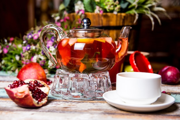 テーブルの上にザクロと白いカップと赤いフルーツティー。