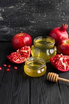 黒い木製のテーブルの上の赤い果物と蜂蜜