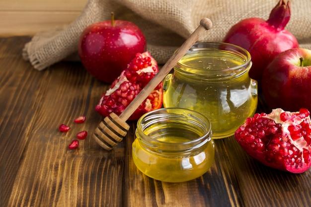 木製の素朴なテーブルの上の赤い果物と蜂蜜