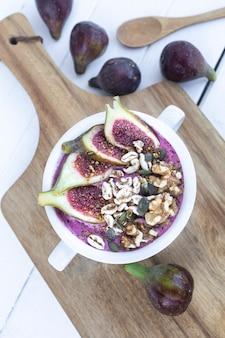 イチジクのシリアルとナッツの赤いフルーツのスムージー朝食用のヘルシーでビーガンのボウル