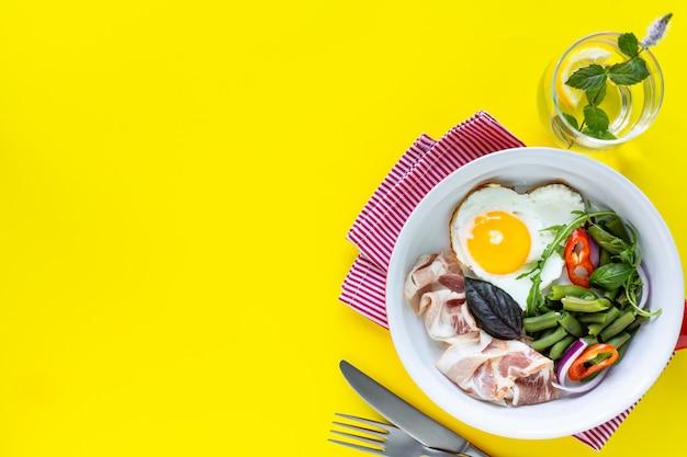 Красная сковорода с вкусным завтраком на желтом фоне, копией пространства. вид сверху, выборочный фокус.