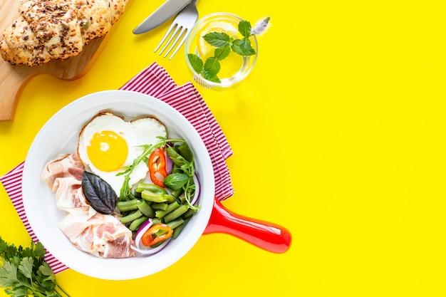 黄色の背景、コピー領域においしい朝食と赤いフライパン。トップビュー、セレクティブフォーカス。