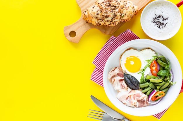 Красная сковорода с очень вкусным завтраком на желтом цвете, космосом экземпляра. вид сверху, выборочный фокус.