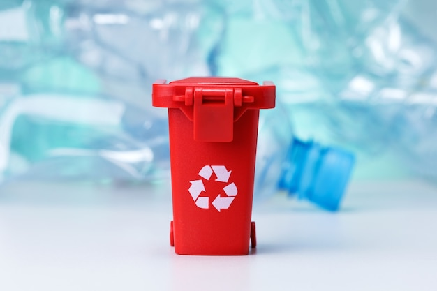 Красный мусорный бак на фоне многих используемых пластиковых бутылок. проблема утилизации.