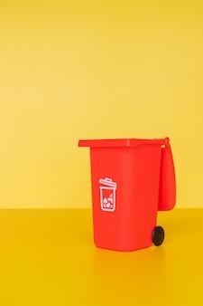黄色の背景に赤いゴミ箱