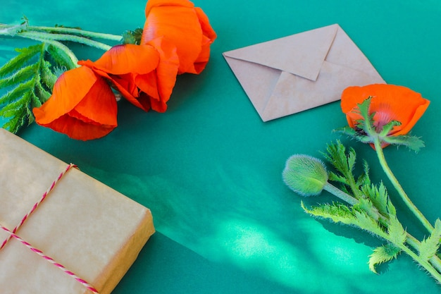 Red garden poppies, a letter, and a gift box on green background