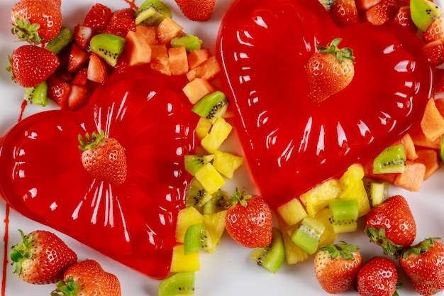 Red gelatin heart shape with chopped fresh fruit on a white table