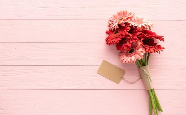 誕生日おめでとう。赤いガーベラの花とピンクの木製テーブルに空白のクラフトラベルタグ、フラットレイ