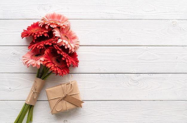 誕生日おめでとう。赤いガーベラの花と白い木製のテーブルにラベルタグ付きのクラフトギフトボックス、フラットレイ