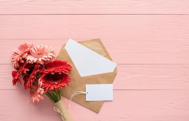 誕生日おめでとう。赤いガーベラの花、封筒、ピンクの木製テーブルの空白のラベルタグ