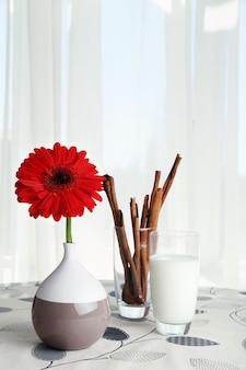 カーテンの上のテーブルにミルクとシナモンのスティックのガラスと赤いガーベラの花